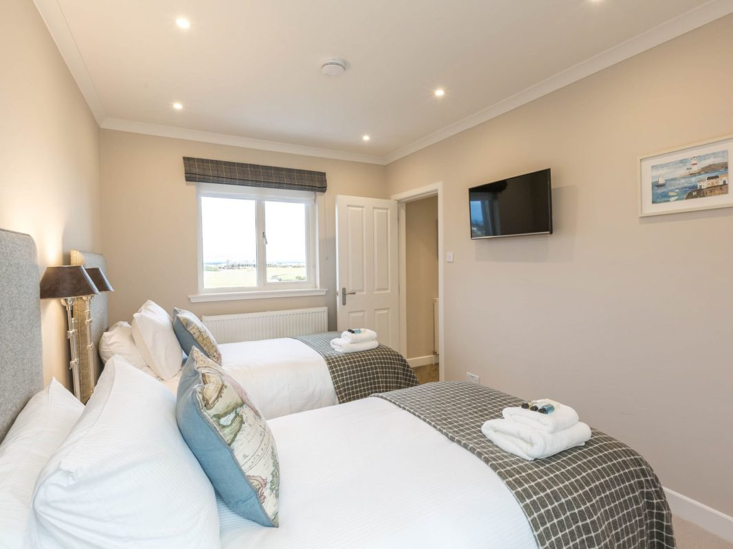 Two singles beds and a wall mounted TV
